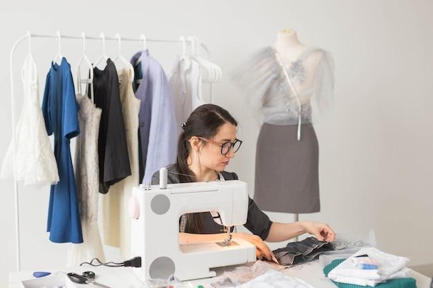 Naaister, mode, kleermaker en mensenconcept - jonge vrouwelijke modeontwerper die in haar showroom werkt.