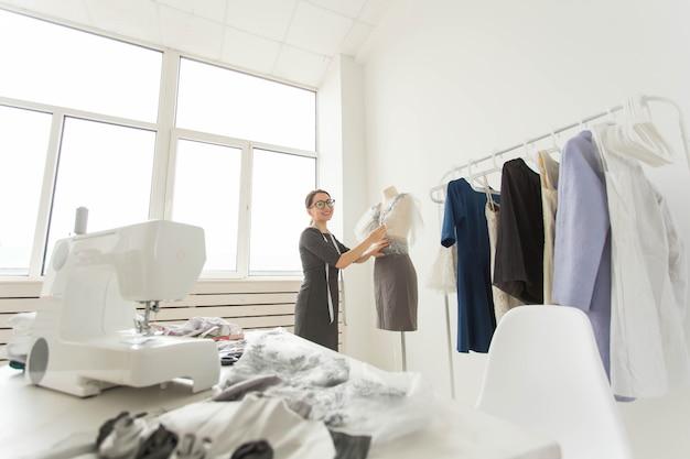 Naaister, modeontwerper en kleermaker concept - designer versiert de outfit op de paspop