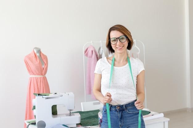 Naaister, modeontwerper en kleermaker concept - jonge naaister vrouw met het naaien op witte muur.