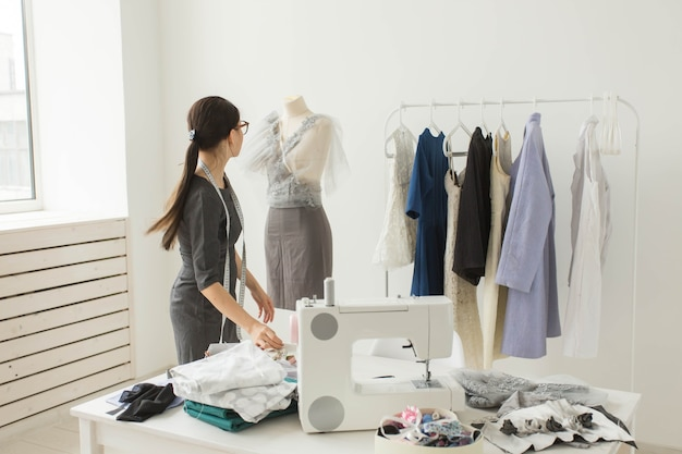 Naaister, modeontwerper en kleermaker concept - werkproces, ontwerper versiert de outfit op