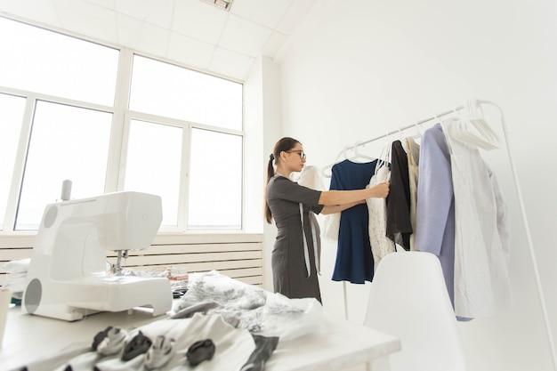 Naaister, modeontwerper en kleermakerconcept - ontwerper kiest de jurken op het rek