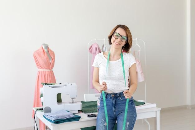 Naaister, modeontwerper, kleermaker en mensenconcept - mooie modevrouwontwerper die zich in studio bevindt