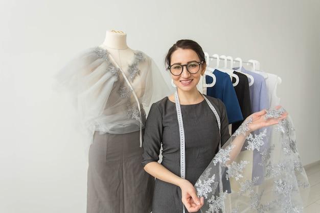Naaister, modeontwerper, kleermaker en mensenconcept - mooie modevrouwontwerper status