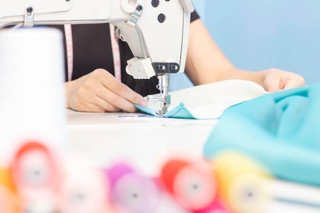 Naaister naaien op een naaimachine close-up. een set items voor handwerk: draden, naalden, pinnen, schaar, meetlint, enz.