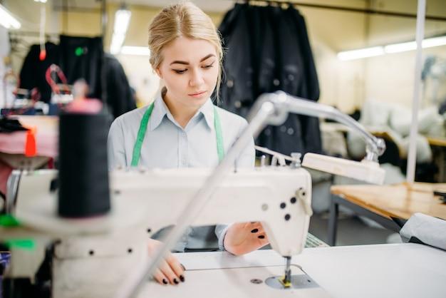 Naaister naait stoffen op een naaimachine. afstemming of kleermakerij op kledingfabriek, handwerk, vrouwelijke naaister in werkplaats