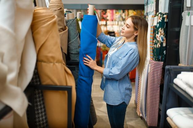 Naaister neemt stofrol in textielatelier. vrouw werkt met stof om te naaien, vrouwelijke kleermaker op het werk, naaister