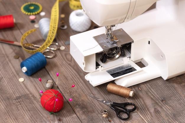 Naaister of kleermakerachtergrond met naaiende hulpmiddelen, kleurrijke draden, naaimachine en toebehoren.
