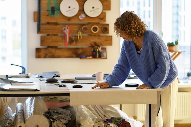 Naaister ontwerp papieren patronen op textiel met krijt en liniaal kleding ontwerper werk in studio