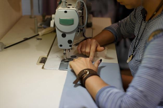 Naaister op de werkplek, kleermakersindustrie, meisje naait op de naaimachine, fabriekskleding,
