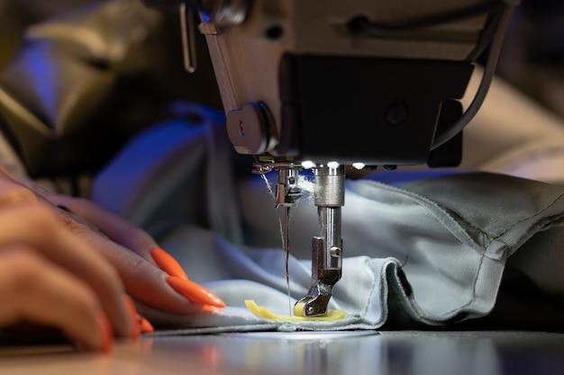 Naaister werk aan naaimachine close-up vrouw modeontwerper maakt nieuwe kledingcollectie