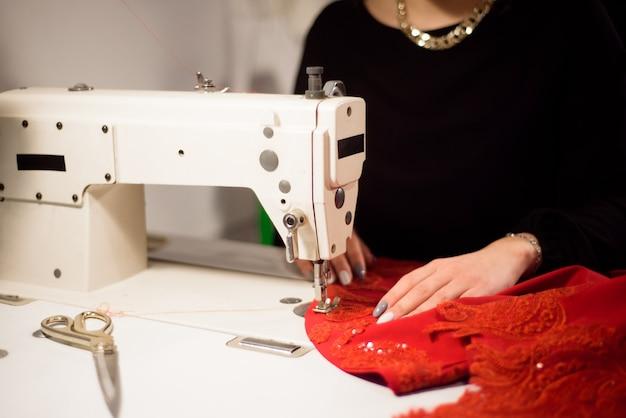 Naaister werkt aan de naaimachine. op maat maken van een kledingstuk. hobbynaaien als klein bedrijfsconcept.