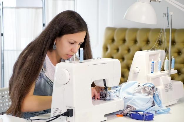 Naaister werkt aan het naaien op een naaimachine in het kleermakerswerk.