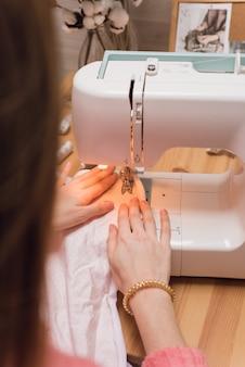 Naaister werkt op een naaimachine. de vrouw naait en houdt een roze doek vast