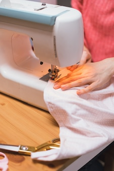 Naaister werkt op een naaimachine. het meisje naait en houdt een roze doek vast