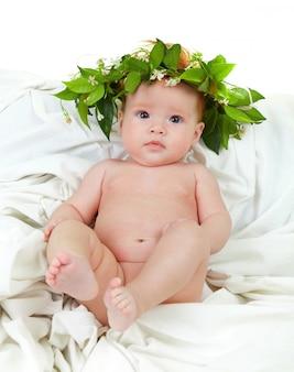 Naakt babymeisje met bloemkroon van jasmijn