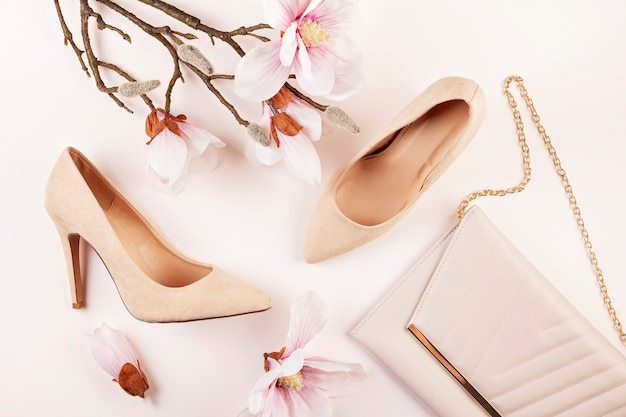 Naakt gekleurde hoge hakken schoenen en magnolia bloemen