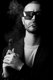 Naakt mannelijk model in de schaduw als een gangster met een wapen