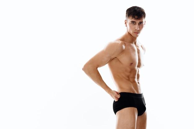 Naakt mannelijke atleet poseren op een lichte achtergrond bijgesneden weergave van zwart slipje model