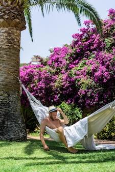 Naakt mannetje ontspannen in een hangmat in de tuin.