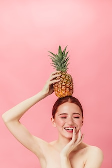 Naakt meisje met ananas lachend met gesloten ogen. studio shot van gember jonge dame met exotisch fruit.