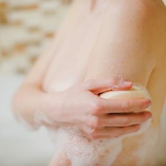 Naakt vrouw zeepende lichaam