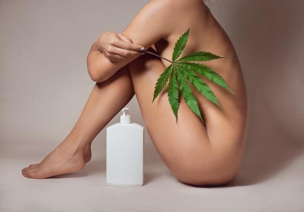 Naakt vrouwenlichaam met cbd huidcrème gemaakt van cannabisextract voor een natuurlijke huidbehandeling. geïsoleerd op grijze achtergrond