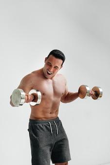 Naakte atleet voert helder en emotioneel oefeningen uit met halters.
