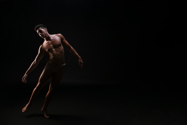Naakte atletische gebogen man die op zwarte achtergrond