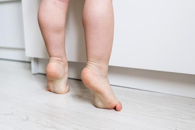 Naakte baby's voeten close-up staande op de tenen. kind staat op zijn tenen. ontwikkeling van een gezond kind. kleine ballerina uit de kindertijd