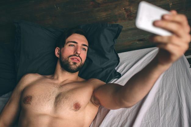Naakte bebaarde donkerharige knappe man zonder shirt in wit bed een selfie maken