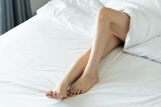 Naakte benen van een jonge vrouwenslaap op haar bed thuis