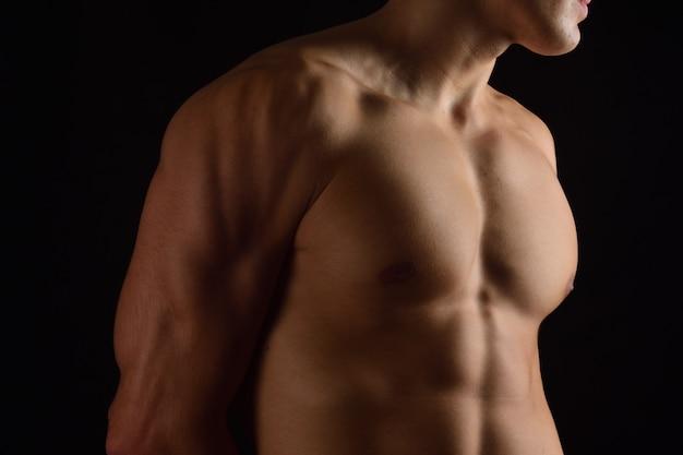 Naakte borst van een man op zwarte achtergrond