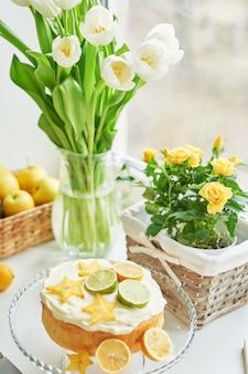Naakte cake met citroenen en limoenen en bloemen
