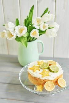 Naakte cake met citroenen en limoenen en tulpenbloemen