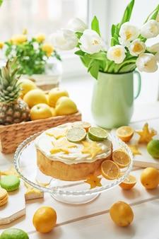 Naakte cake met citroenen en limoenen, fruit en witte tulpen