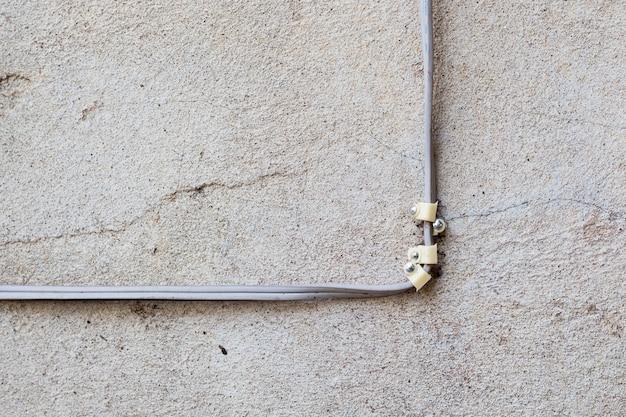 Naakte concrete muur met elektro bedrading als achtergrond