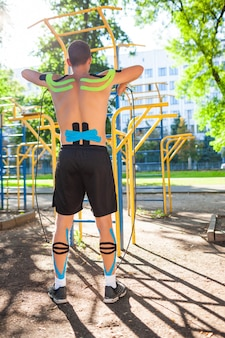 Naakte gespierde man training met fitness touw op sportveld. achteraanzicht van jonge onherkenbare bodybuilder met elastische kinesiologie taping op lichaamstraining buitenshuis. revalidatieconcept.