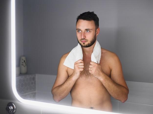 Naakte jonge man in de spiegel kijken