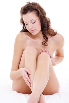 Naakte jonge vrouw die haar lange benen, zittend op het bed, in de watten legt