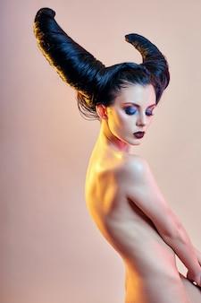 Naakte kunstvrouw met haar in de vorm van hoorns, een vrouwelijke demon