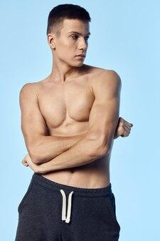 Naakte man in korte broek en sloeg zijn armen over zijn borst en keek naar de zijkant bodybuilder fitness sport