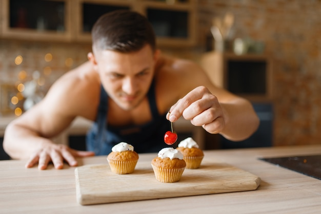 Naakte man in schort dessert op de keuken koken