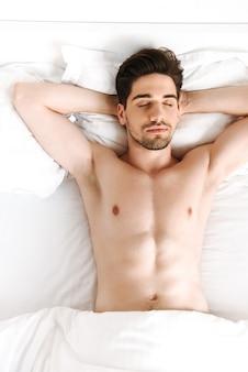 Naakte man slapen in bed binnenshuis thuis.