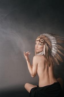 Naakte perfecte vrouw in het gewaad van amerikaanse indianen in de rook