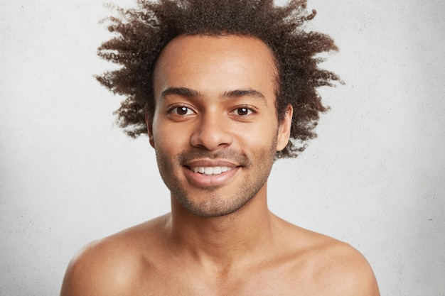 Naakte positieve afro-amerikaanse man met een donkere, gezonde huid en krullend haar, glimlacht zachtjes