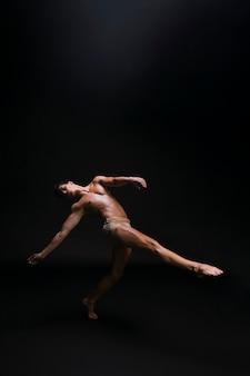 Naakte sierlijke man dansen tegen zwarte achtergrond