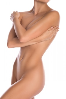 Naakte vrouw die haar mooie lichaam bedekt met handen