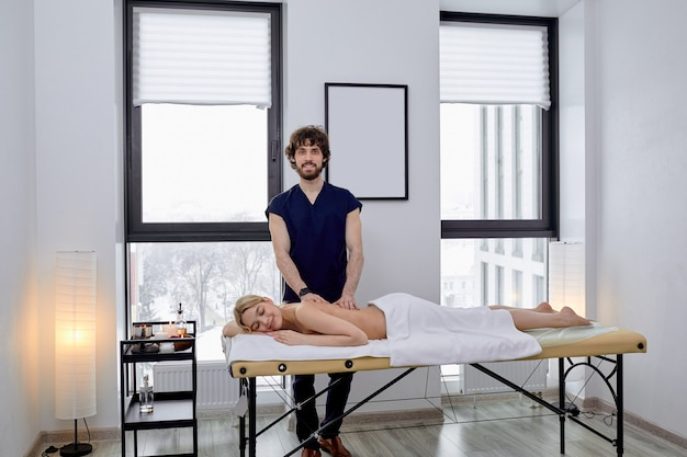 Naakte vrouw die van massage geniet. zijaanzicht op halfnaakte blondine met perfect lichaam, liggend op haar buik en masseurhanden die haar rug masseren, vrije ruimte