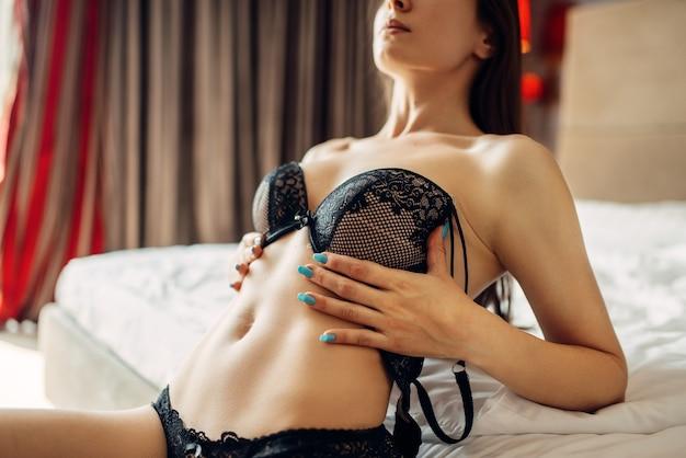 Naakte vrouw in erotisch zwart ondergoed liggend in bed, slaapkamer interieur. naakt vrouwelijk model vormt voor de camera