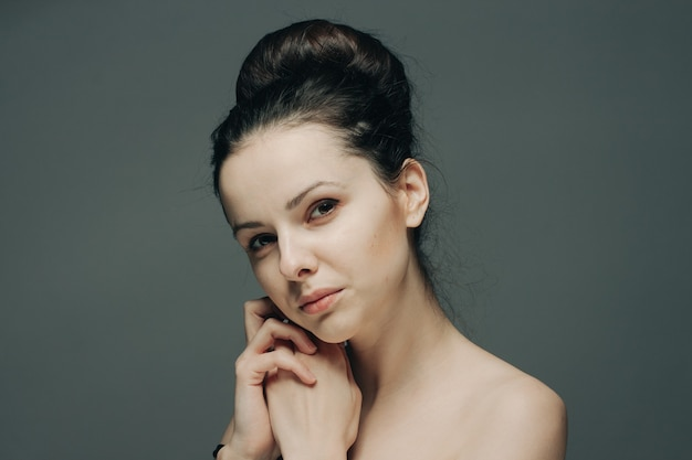 Naakte vrouw met kapsels in haar hoofd raakt haar gezicht met haar handen op een grijze achtergrond